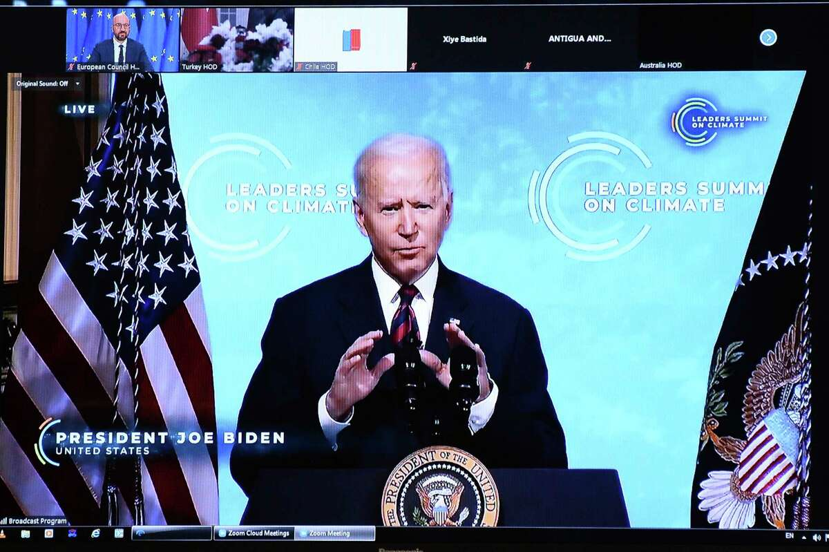 U.S. President Joe Biden is seen on a screen as European Council President Charles Michel attends a virtual Global Climate Summit via video link from the European Council building in Brussels, Thursday, April 22, 2021. (Johanna Geron, Pool via AP)