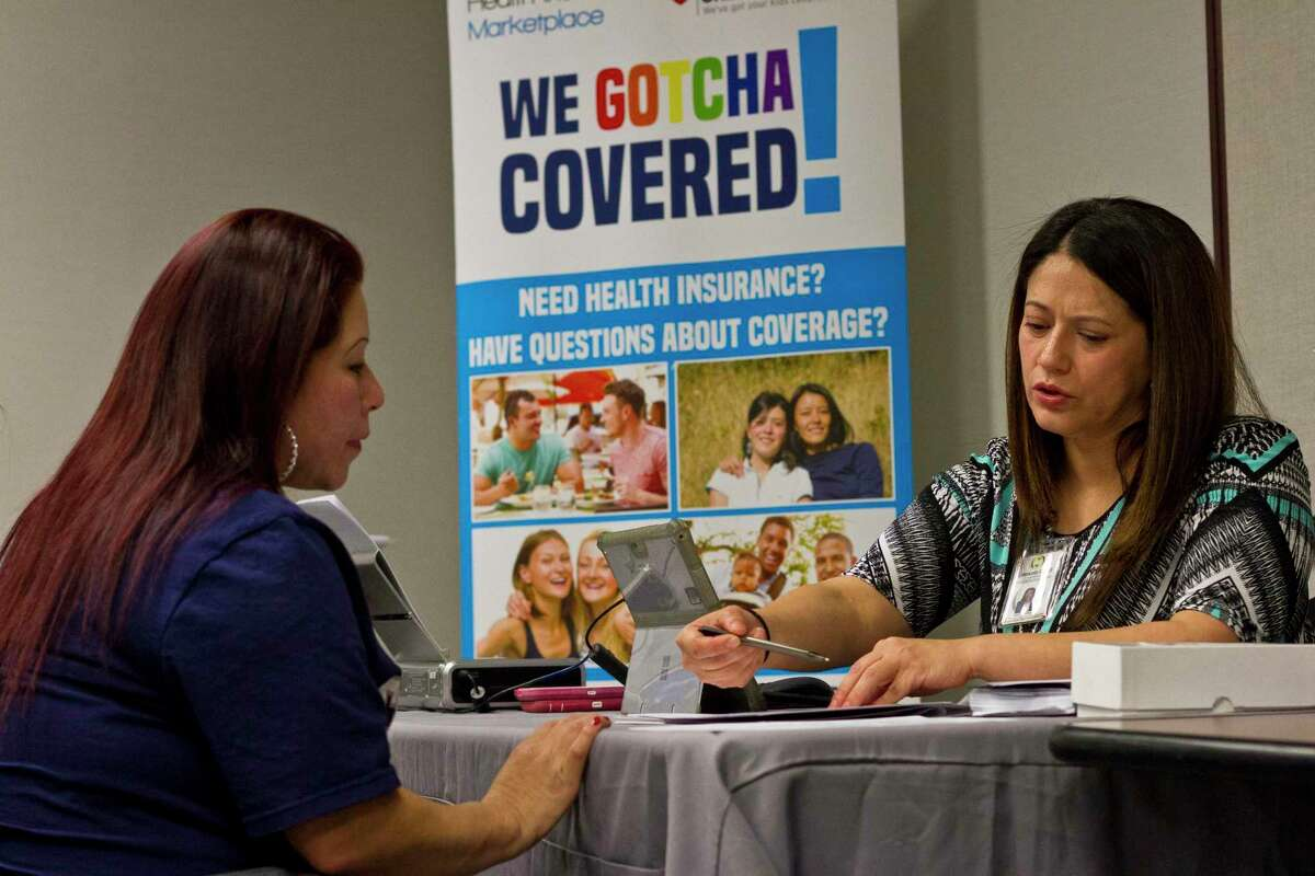 Maria del Carmen Romero, right, helps a woman understand health care coverage through the Affordable Care Act in Dallas, Jan. 30, 2017. Texas, in the midst of a surge of coronavirus cases, asked the Supreme Court on Thursday to overturn the Affordable Care Act. (Mark Graham/The New York Times)