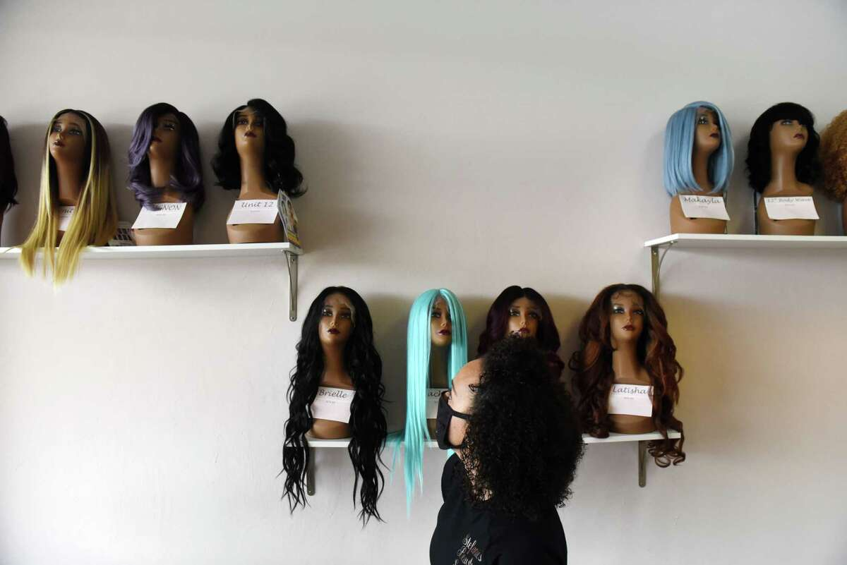 Stefanie Thomas, owner of Stefanie's Beauty Supply, shows some of the wigs displayed at her store on Friday, April 16, 2021, in Clifton Park, N.Y. Thomas opened her beauty supply store in the middle of the pandemic, December 2020. She wanted to open a store that would serve Black mothers and daughters, something she did not have when growing up Black in a white neighborhood. On Thursday, April 22, she held a ribbon cutting ceremony for the store. (Will Waldron/Times Union)