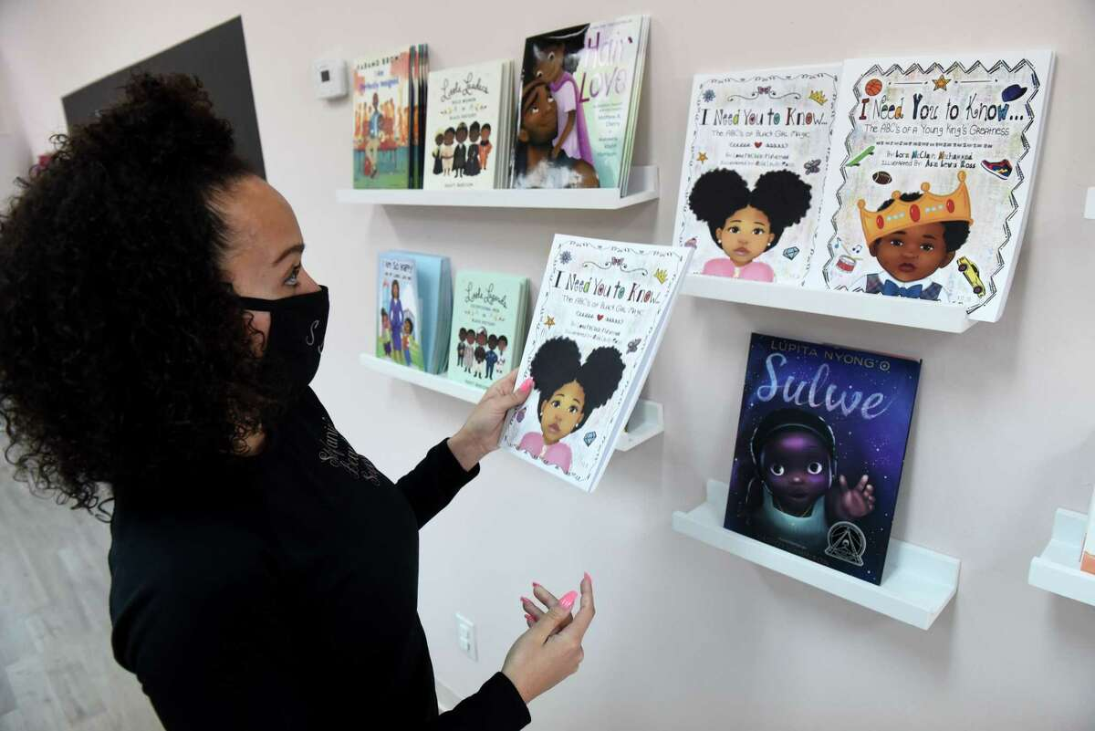 Stefanie Thomas, owner of Stefanie's Beauty Supply, shows some of the self empowering children's books she keeps at her store on Friday, April 16, 2021, in Clifton Park, N.Y. Thomas opened her beauty supply store in the middle of the pandemic, December 2020. She wanted to open a store that would serve Black mothers and daughters, something she did not have when growing up Black in a white neighborhood. (Will Waldron/Times Union)