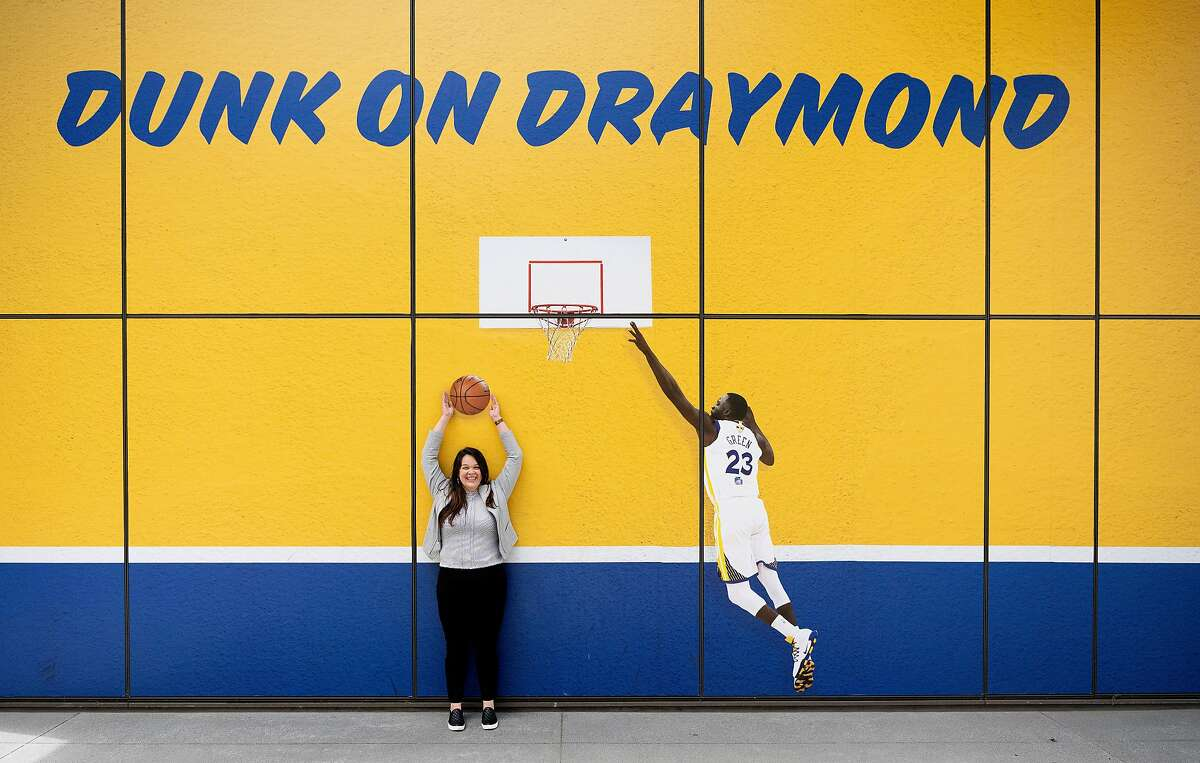 Warriors' director of facility health and hygiene Jackie Ventura poses for a photo in front of a mural at Chase Center.