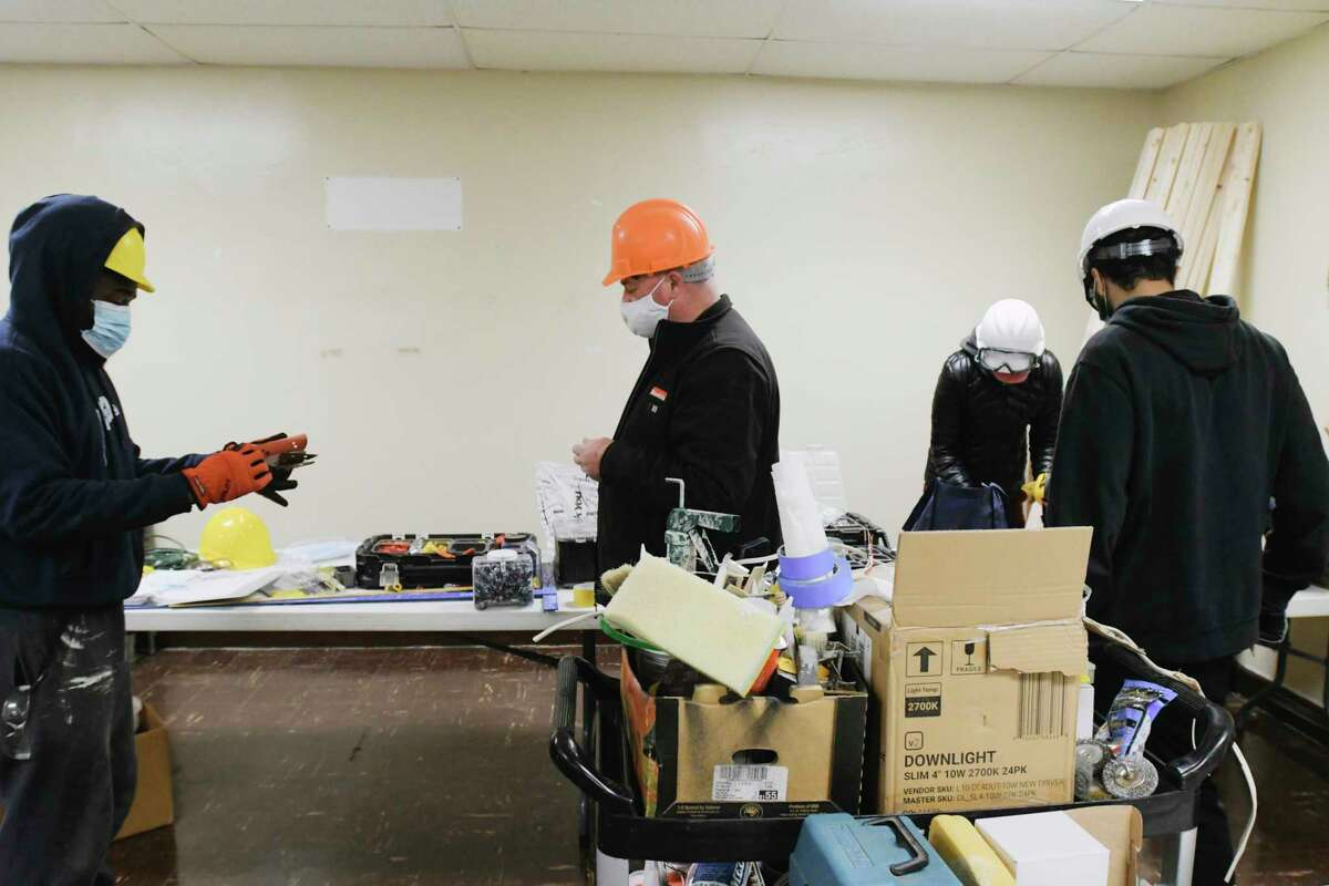 George Vanderwouden, center, a construction instructor with the Help Yourself Win Foundation, talks with the men and women in the program as they work rehabbing the Bethel AME Church on Thursday, April 22, 2021, in Schenectady, N.Y. (Paul Buckowski/Times Union)