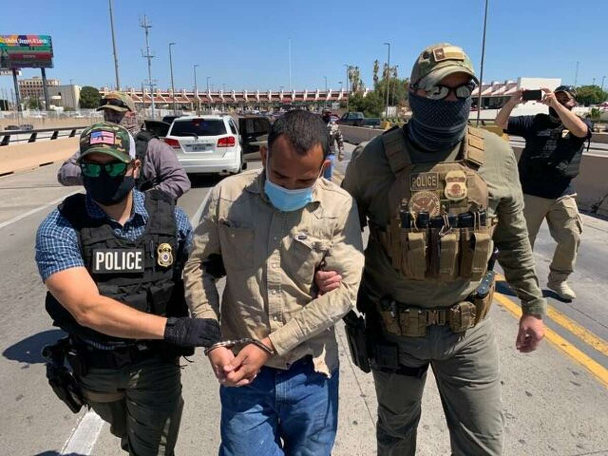 U.S. Immigration and Customs Enforcement's Enforcement and Removal Operations officers escort Francisco Javier Duran-Torres, 37, to the middle of the Juarez-Lincoln International Bridge on Tuesday. Duran-Torres, a Mexican citizen who had crossed the border illegally, was wanted for murder in Mexico since 2008.