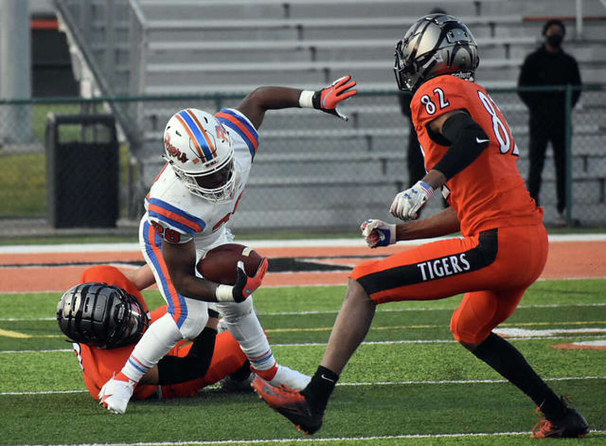 Two members of the Edwardsville defense, including Johnnie Robinson, right, stop East St. Louis running back DeAndre Lawrence for a short gain in the first quarter in Week 3 in Edwardsville.