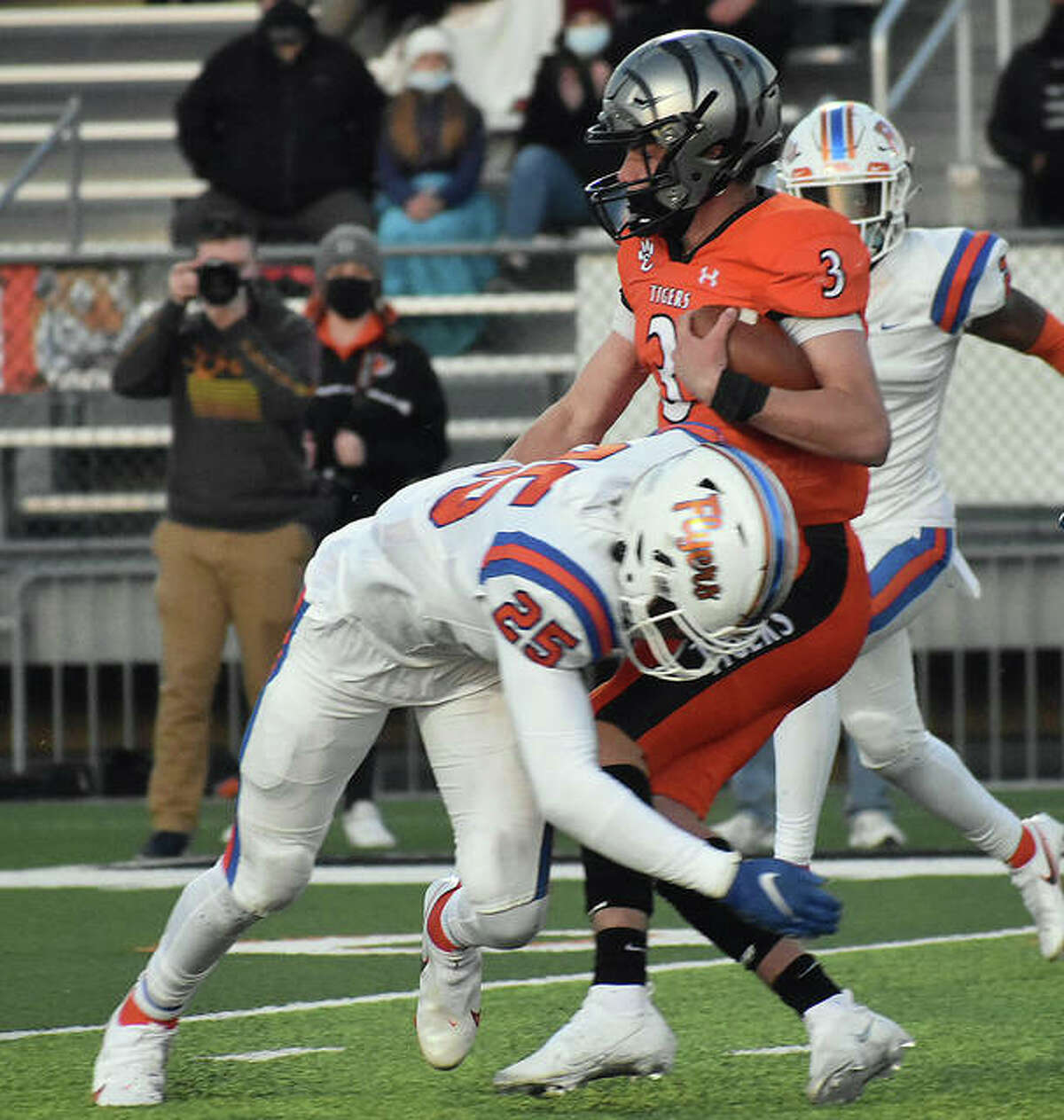 Edwardsville quarterback Ryan Hampton is tackled by East St. Louis safety Dallas Brown in the first quarter.