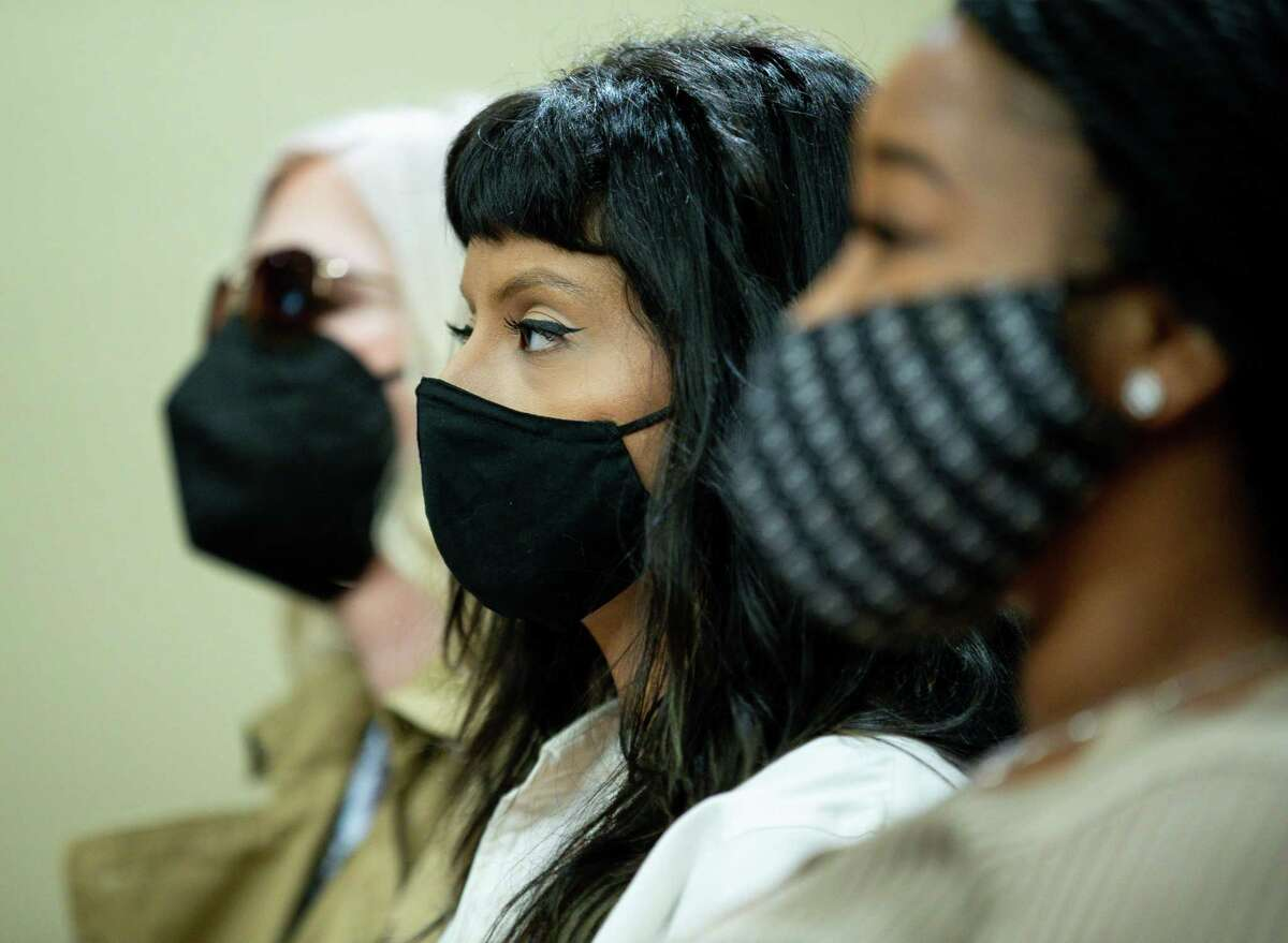 Ashley Solis, center, listens during a hearing in the sexual assault ligitation against Houston Texans quarterback Deshaun Watson in the 113th District Court inside Harris County Civil Courthouse on Thursday, April 22, 2021, in Houston. Solis publicly identified herself during a news conference in early April.