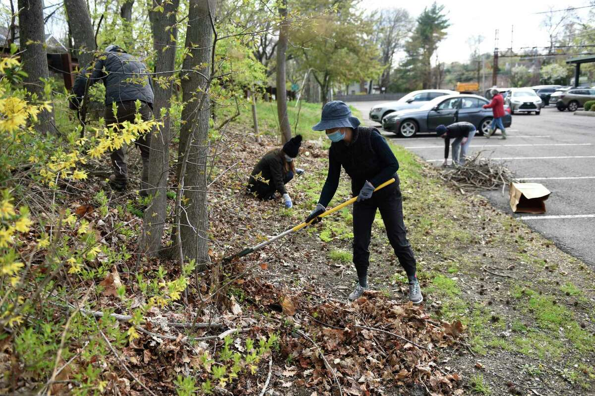 Riverside Garden Club member Sharon Hu participates in an Earth Day cleanup at the Riverside Metro-North station in the Riverside section of Greenwich, Conn. Thursday, April 22, 2021. The volunteers cleaned up trash and beautified the landscape around the Riverside train station.