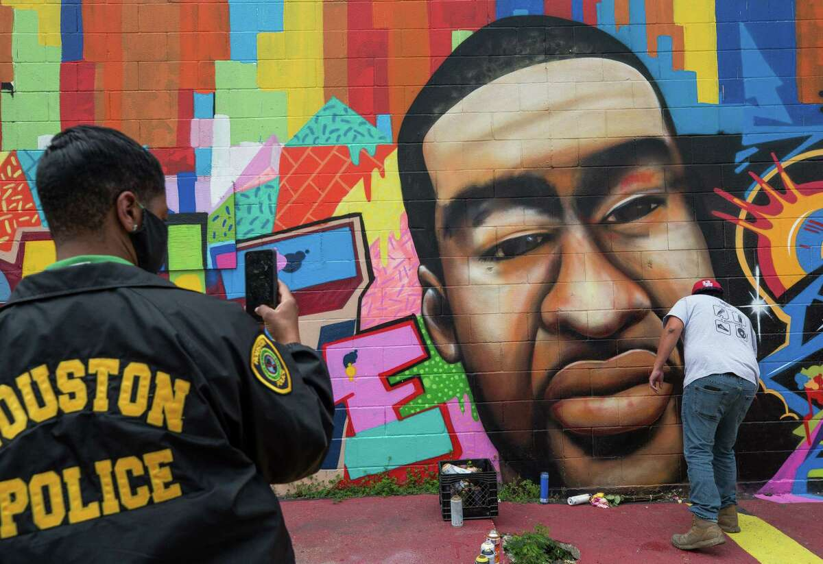 A Houston Police officer takes a photo of a George Floyd mural which was vandalized on Thursday, April 22, 2021, in the East Downtown area in Houston.