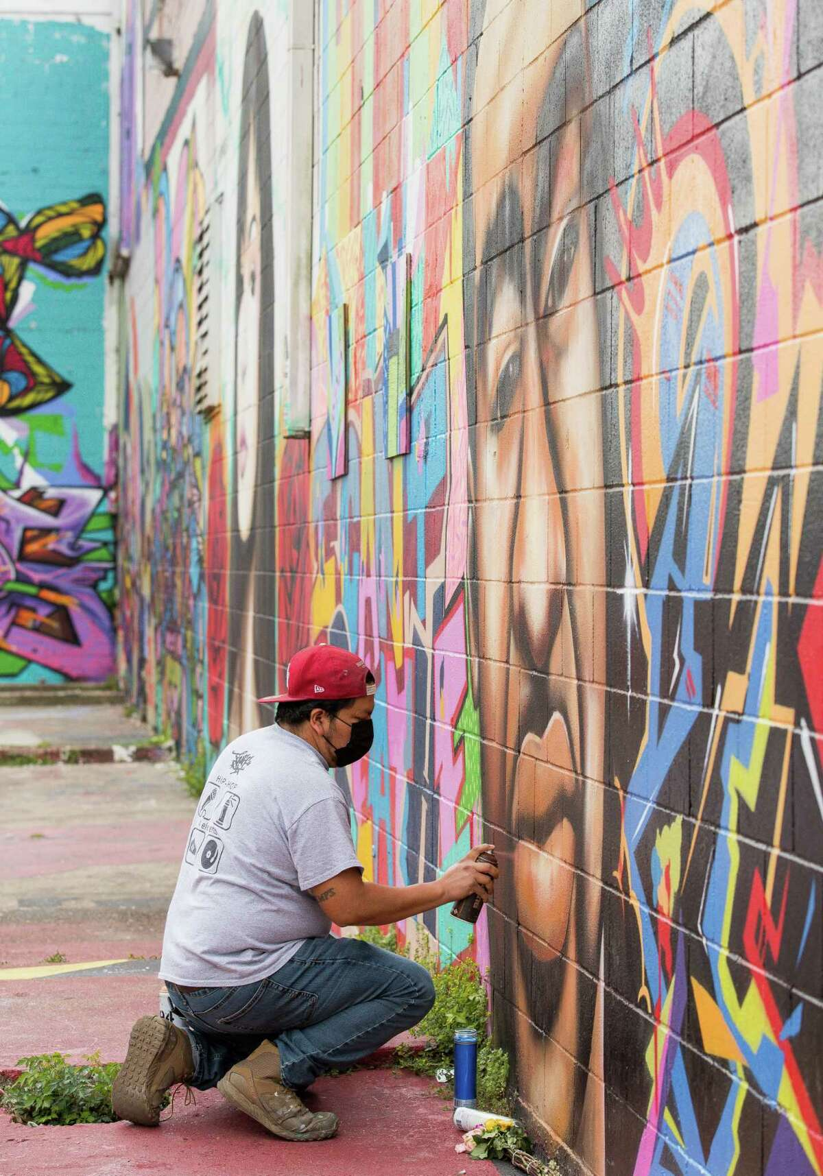 Artist Carlos Alcaraz works to restore a George Floyd mural which was vandalized on Thursday, April 22, 2021, in the East Downtown neighborhood in Houston.