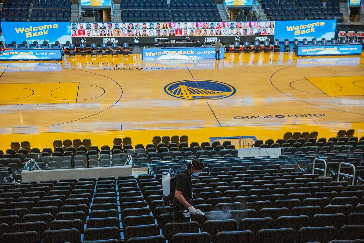 A worker disinfects the seats at Chase Center.