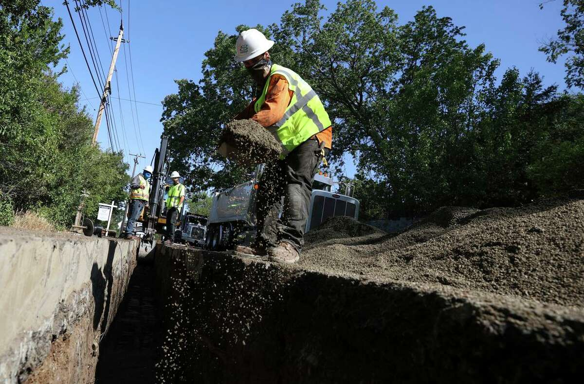This file photograph shows workers with East Bay Municipal Utility District (EBMUD) fill a trench with sand as they install new water pipe on April 22, 2021 in Walnut Creek, California. (Photo by Justin Sullivan/Getty Images)