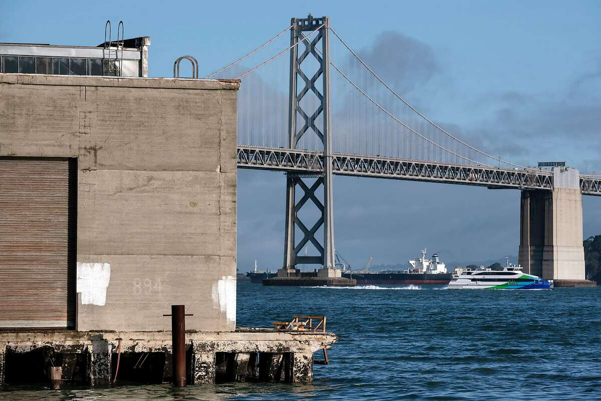 A ferry and tanker ship pass by the Bay Bridge as Pier 38 is seen in the foreground at left, in San Francisco, California. A tanker crewmember has been convicted of dumping oily bilge water into Bay Area waters.