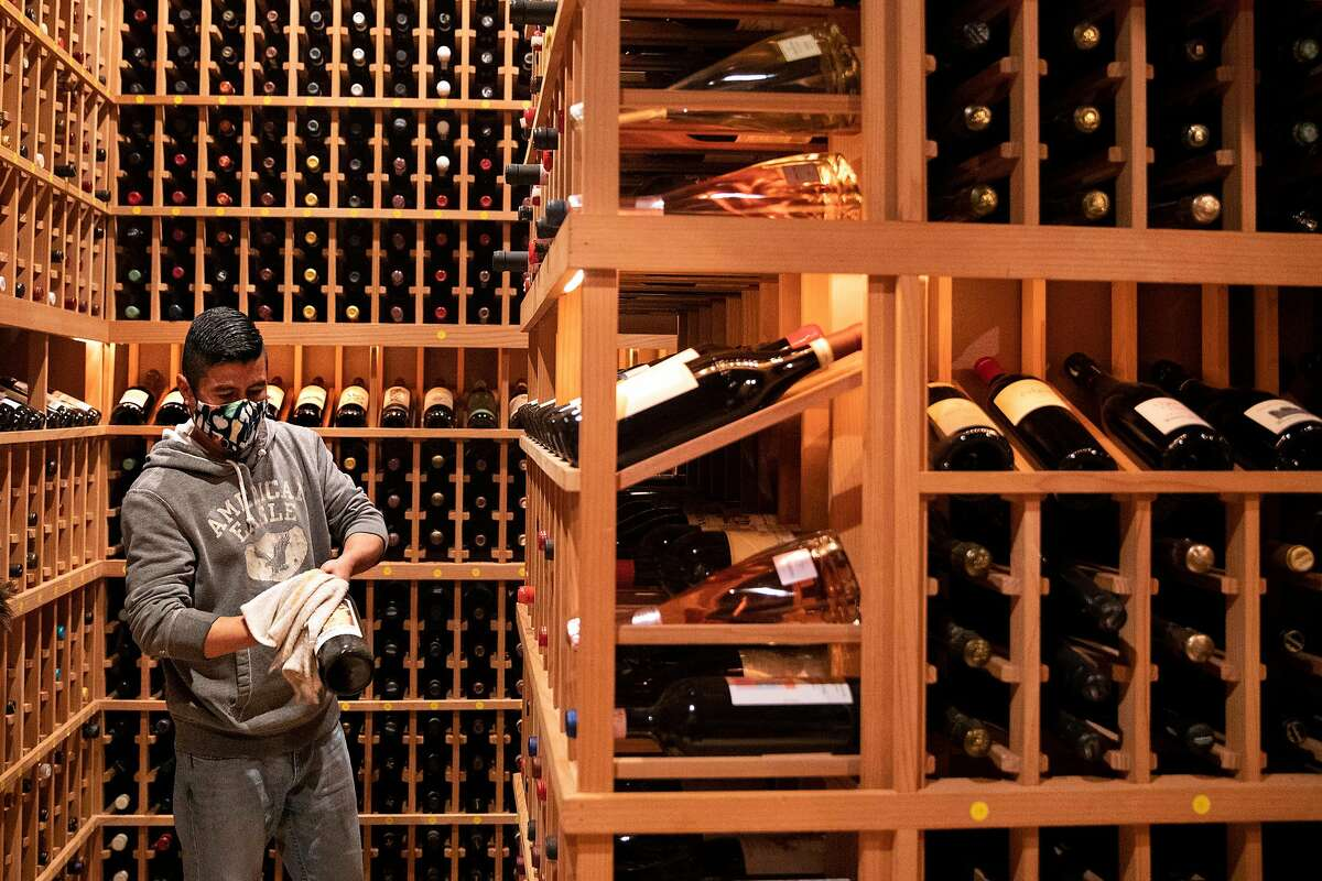 Vidal Mozqueda dusts off bottles of wine that have sat in the cellar untouched since March 2020 as Acquerello in San Francisco prepares for reopening indoor dining next month.