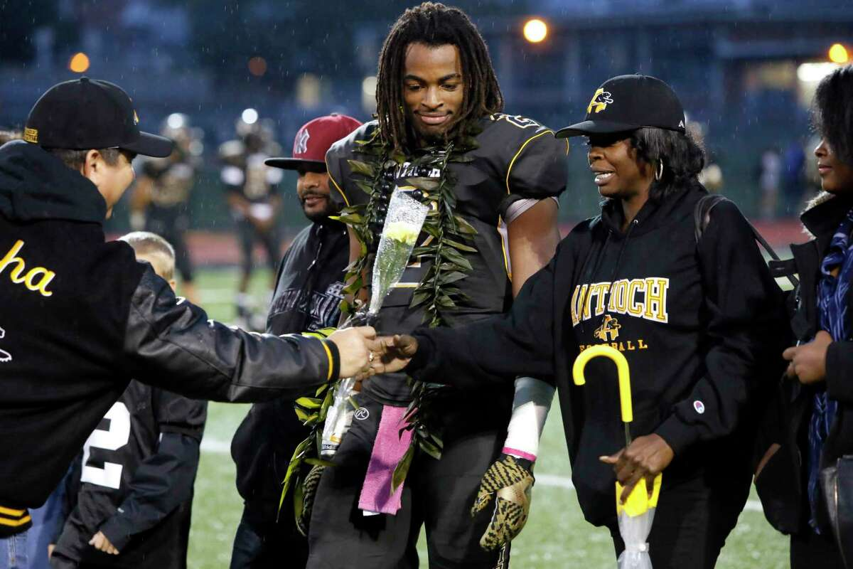 Seniors' night for the players as school principal Louie Rocha, (left) hands a flower to Tianna Hicks with her son Najee Harris , 2 close by as the Antioch Panthers prepare to take on the Heritage Patriots in Antioch, California on Friday October 28, 2016.