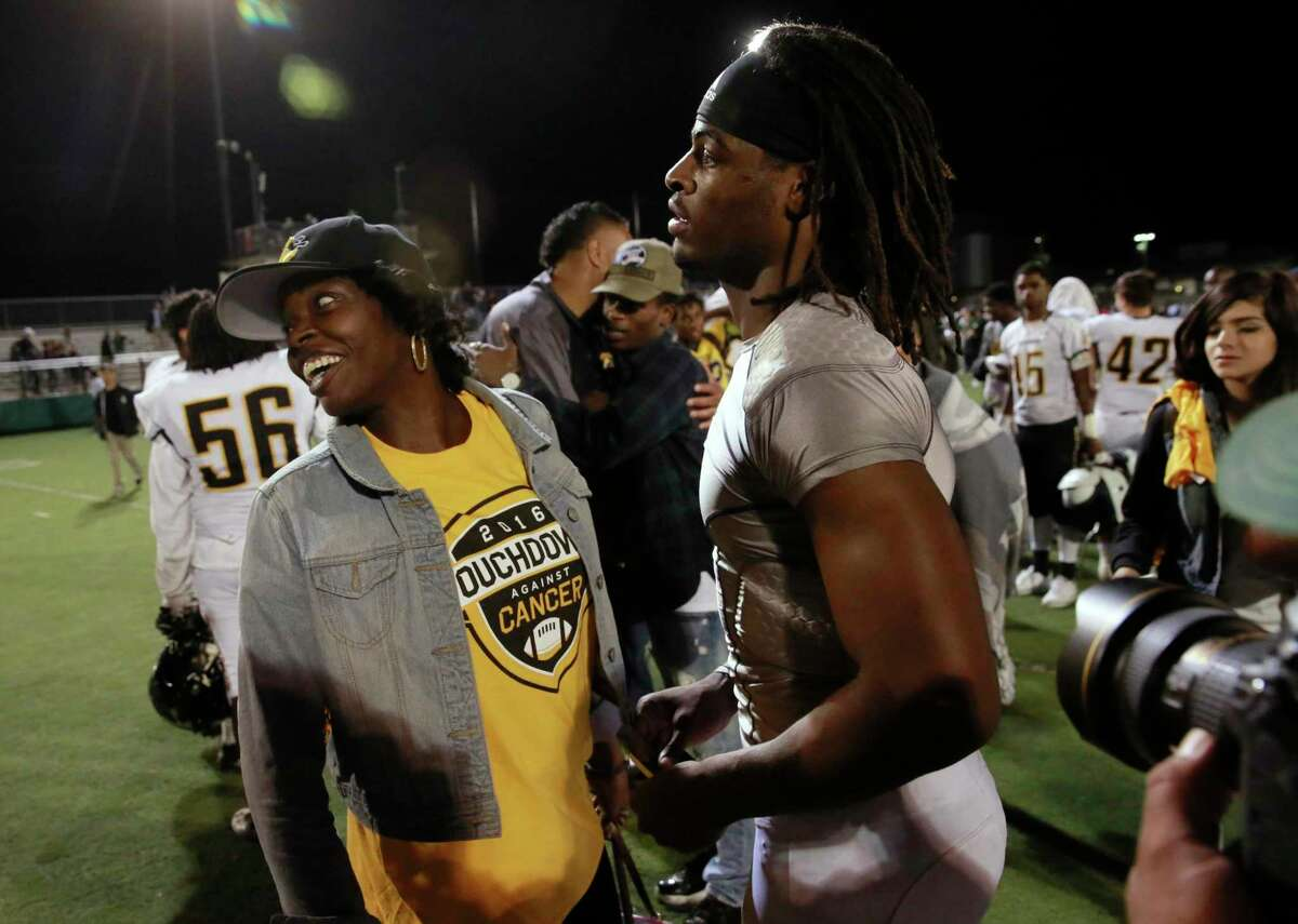 Najee Harris, 2 and his mother Tianna Hicks keep their spirits high and spend time with fans after the Antioch Panthers high school fell 28-21 to the Spartans of De La Salle in Concord, California on Fri. Sept. 23, 2016.
