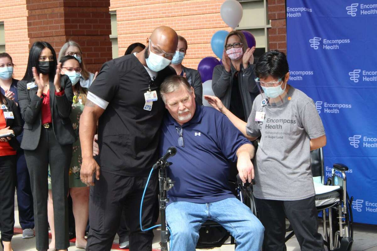 Fort Bend County Sheriff's Office Kevin White hugs a member of the staff at Encompass Health in Sugar Land after being discharged on Wednesday, April 21. White was discharged after receiving rehabilitation needed after he suffered complications from COVID-19