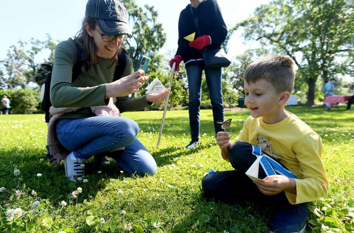 Marcie Lee takes a photo as her son Benjamin holds a piece of clover upon which his butterfly sat as they join in the butterfly release on the opening day of Shangri La's Eco-Fest 2021: Butterflies & Blooms, celebrating Earth Day. The event continues through Saturday. Photo made Thursday, April 22, 2021 Kim Brent/The Enterprise