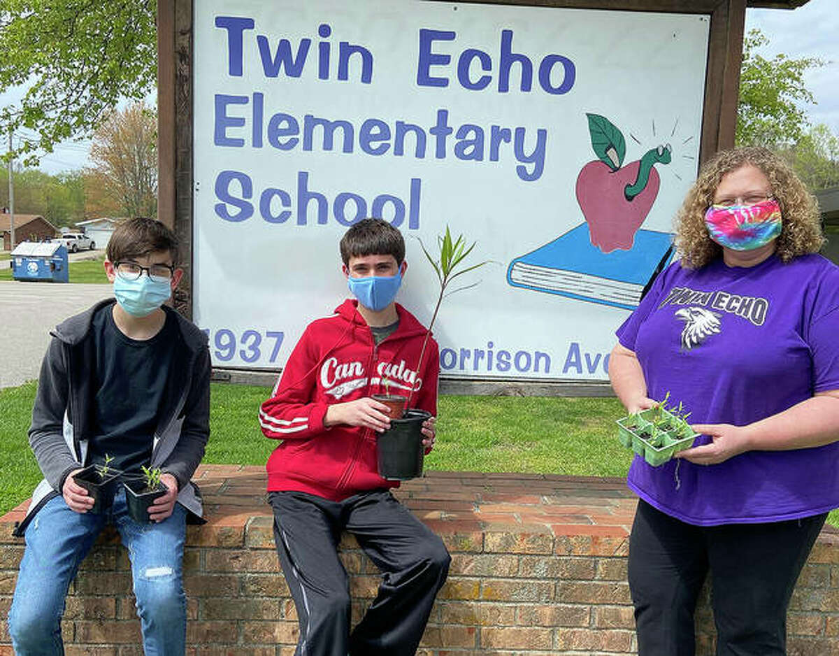 Students Johnny Heinz, left, Elliott Schusky, and fourth-grade teacher Theresa Marlin at Twin Echo Elementary School, show off some of the milkweed plants they received, thanks to efforts from Collinsville High students.