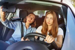 Teenage girl and her mother during driving lesson in a car
