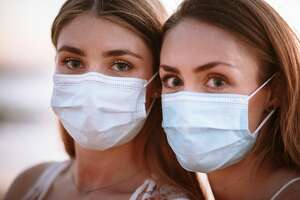 Two young women at a beautiful beach at sunset, wearing protective face masks because of COVID-19