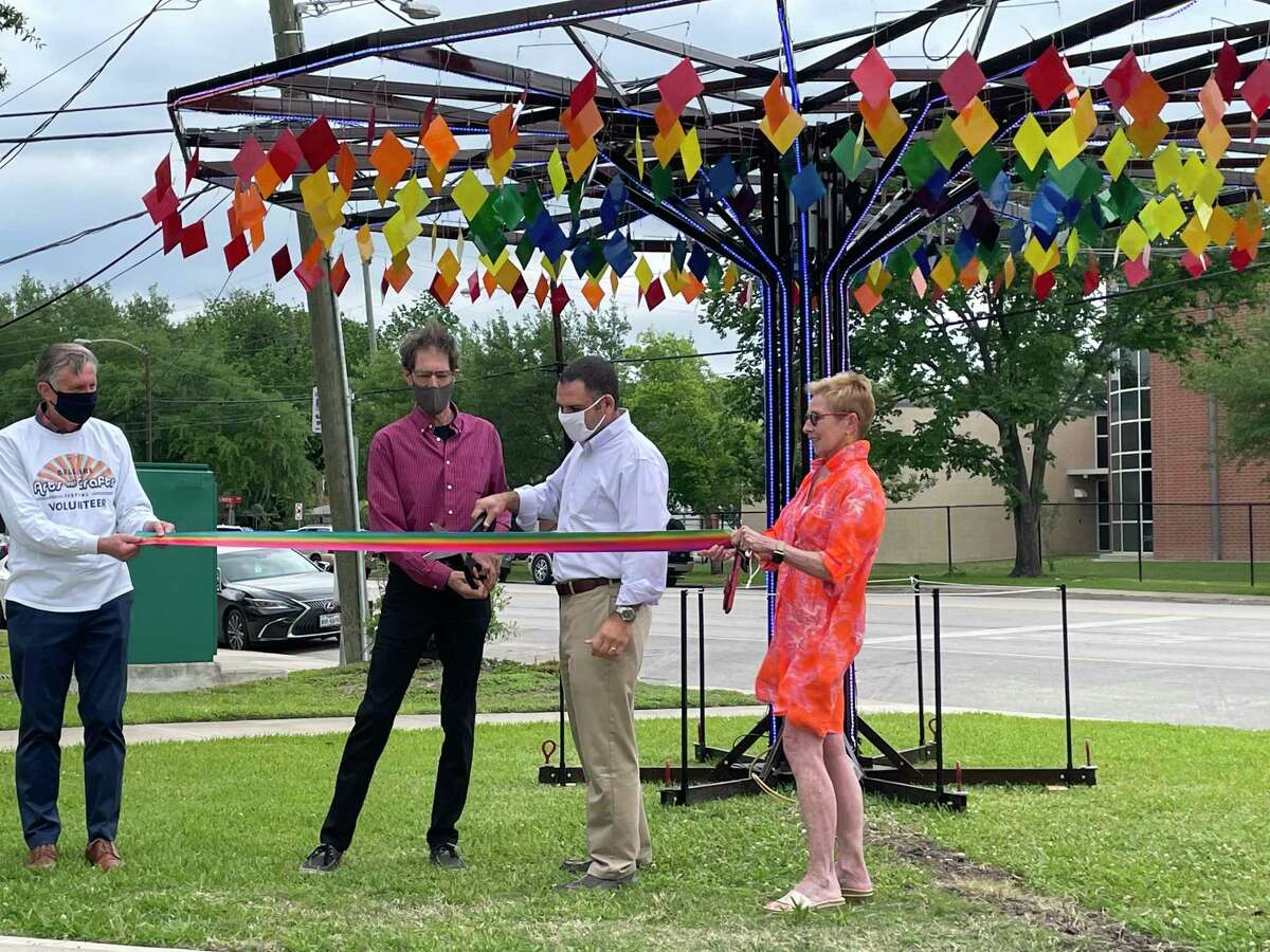 Artist Paul Robertson (in the red shirt) and City of Bellaire mayor Andrew Friedberg (in the white shirt) cut the ribbon for Robertson's art piece Oasis Art Tree during a ceremony on the afternoon of April 22. The piece which is now on public display at Loftin Park right next to Bellaire City Hall.