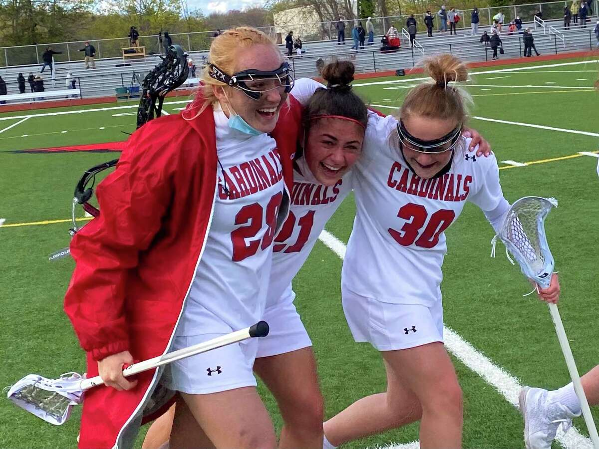 Greenwich's Rylan Sepot is embraced by Kaitlyn Kelly and Cece Tauber after rallying for an 11-10 win over Staples on Thursday.