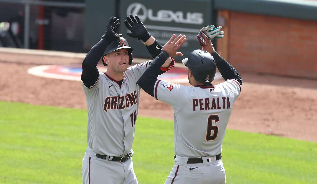 Arizona's Carson Kelly celebrates with David Peralta after hitting a home run in the 10th inning.