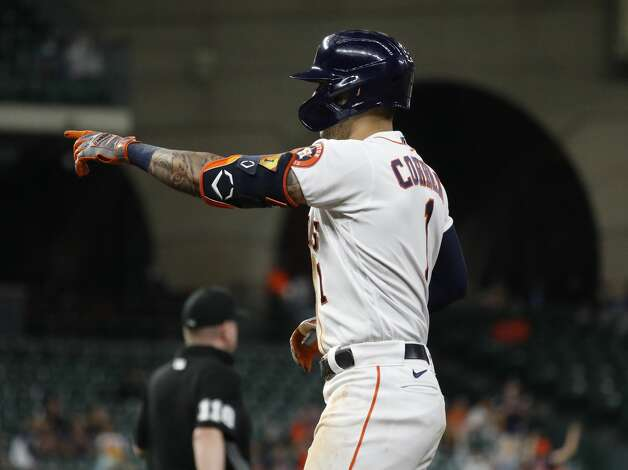 Houston Astros Carlos Correa (1) points to Martin Maldonado as he crosses the plate after Correa's RBI single during the third inning of an MLB baseball game at Minute Maid Park, Thursday, April 22, 2021, in Houston. Photo: Karen Warren/Staff Photographer / @2021 Houston Chronicle