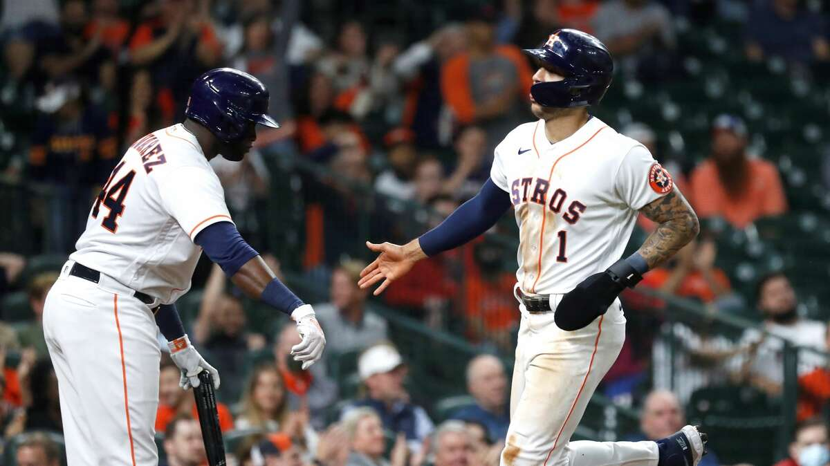 Houston Astros Carlos Correa (1) celebrates with Yordan Alvarez (44) after scoring a run on Alex Bregman's single during the fifth inning of an MLB baseball game at Minute Maid Park, Thursday, April 22, 2021, in Houston.
