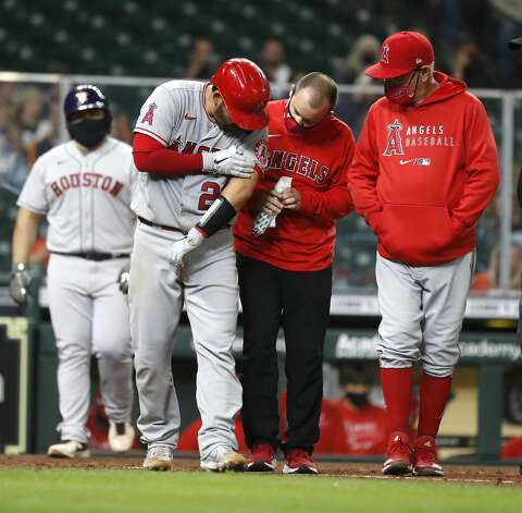 A trainer looks at Los Angeles Angels Kurt Suzuki's elbow after getting hit by a pitch from Houston Astros pitcher Bryan Abreu (66) during the seventh inning of an MLB baseball game at Minute Maid Park, Thursday, April 22, 2021, in Houston. Photo: Karen Warren/Staff Photographer / @2021 Houston Chronicle