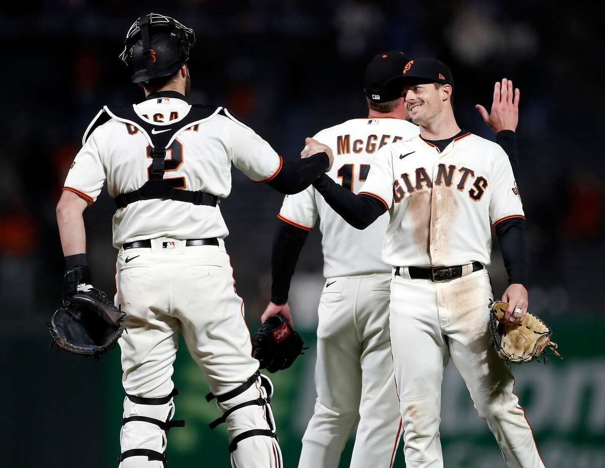 Mike Yastrzemski (right) congratulates Curt Casali after the game, which was the fifth consecutive shutout caught by Casali.