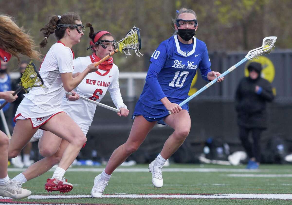 Darien's Sadie Stafford (10) controls the ball while being pressured by New Canaan's Dillyn Patten and Kaleigh Harden (6) during a girls lacrosse game at Dunning Field on Thursday, April 22, 2021.