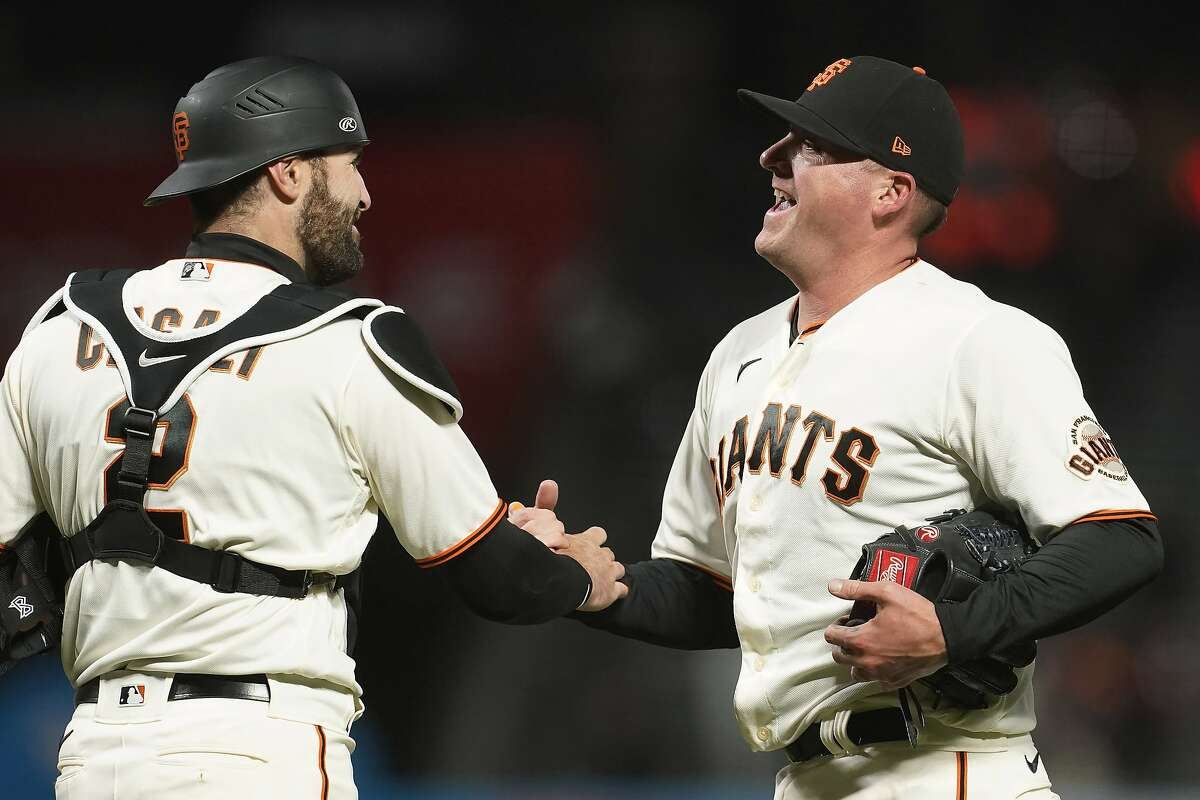 San Francisco Giants catcher Curt Casali, left, celebrates with relief pitcher Jake McGee after the Giants defeated the Miami Marlins in a baseball game in San Francisco, Thursday, April 22, 2021. (AP Photo/Jeff Chiu)