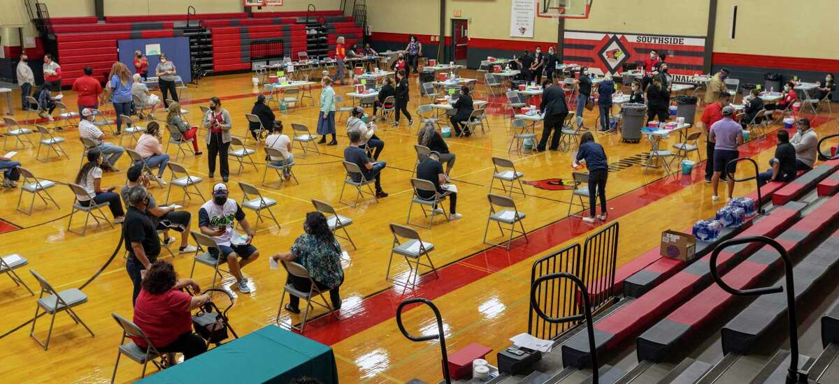 Some people sit the required 6-foot social distance away from each other Saturday, April 11, 2021, at Southside High School as they wait the required 15 minutes after they received the Johnson & Johnson COVID-19 vaccine while other people receive theirs during a clinic sponsored by the University of the Incarnate Word and Southside ISD. The more people get vaccinated, the closer the community gets to the goal of herd immunity, the point at which a majority of people are immunized and the chances of getting the disease are greatly reduced.