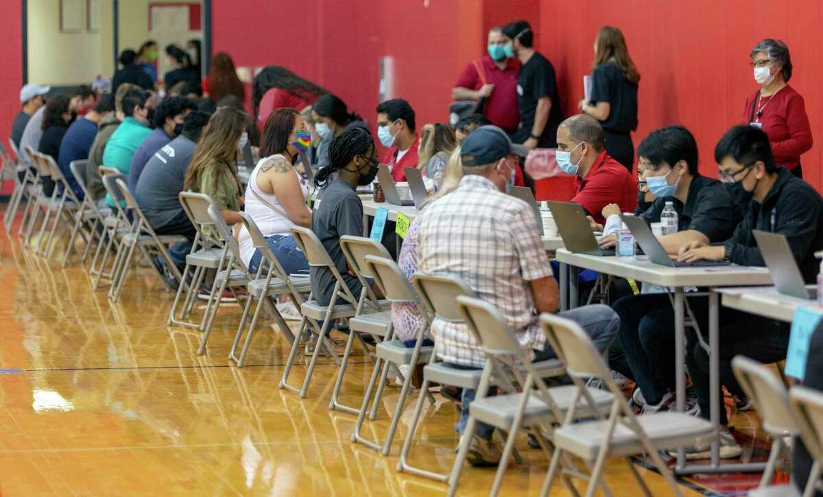 People register Saturday, April 11, 2021 at Southside High School for their COVID-19 vaccine during a University of the Incarnate Word and Southside ISD vaccination clinic. The event had 1,000 doses of the single-shot Johnson & Johnson vaccine to administer.