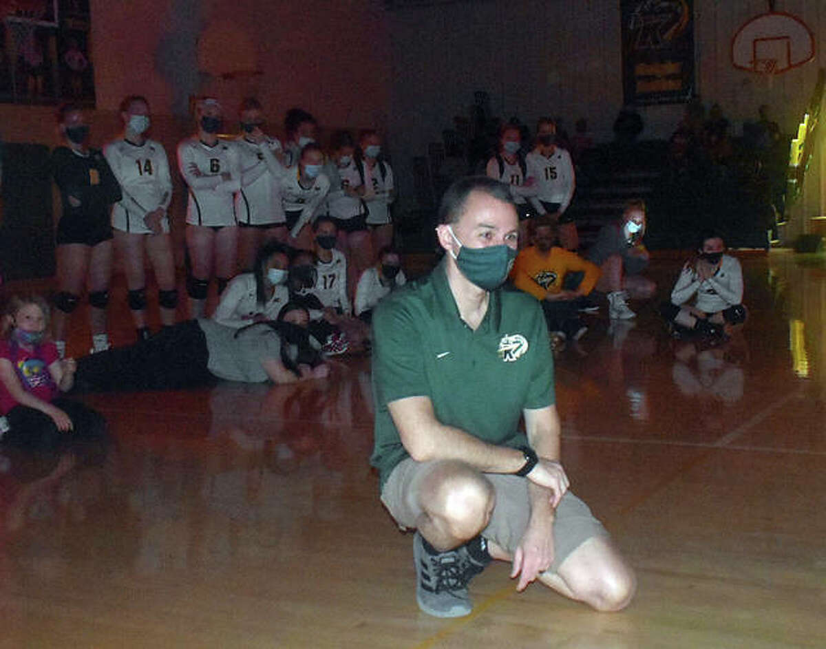 Metro-East Lutheran girls volleyball coach Jon Giordano watches a 10-minute video from his former players congratulating him on his career prior to the match against Father McGivney on Monday.