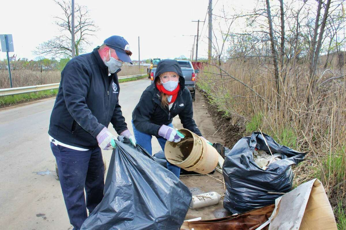 Public Works Commissioner Tom J. McCarthy holds a trash bag while Mayor Nancy R. Rossi disposes of a plastic bucket found in a marsh off Spring Street during the city's Earth Day cleanup April 22.