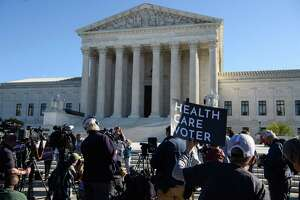 A demonstrator holds a sign in front of the US Supreme Court in Washington, D.C., on Nov. 10, 2020, as the high court opened arguments in the long-brewing case over the constitutionality of the 2010 Affordable Care Act.