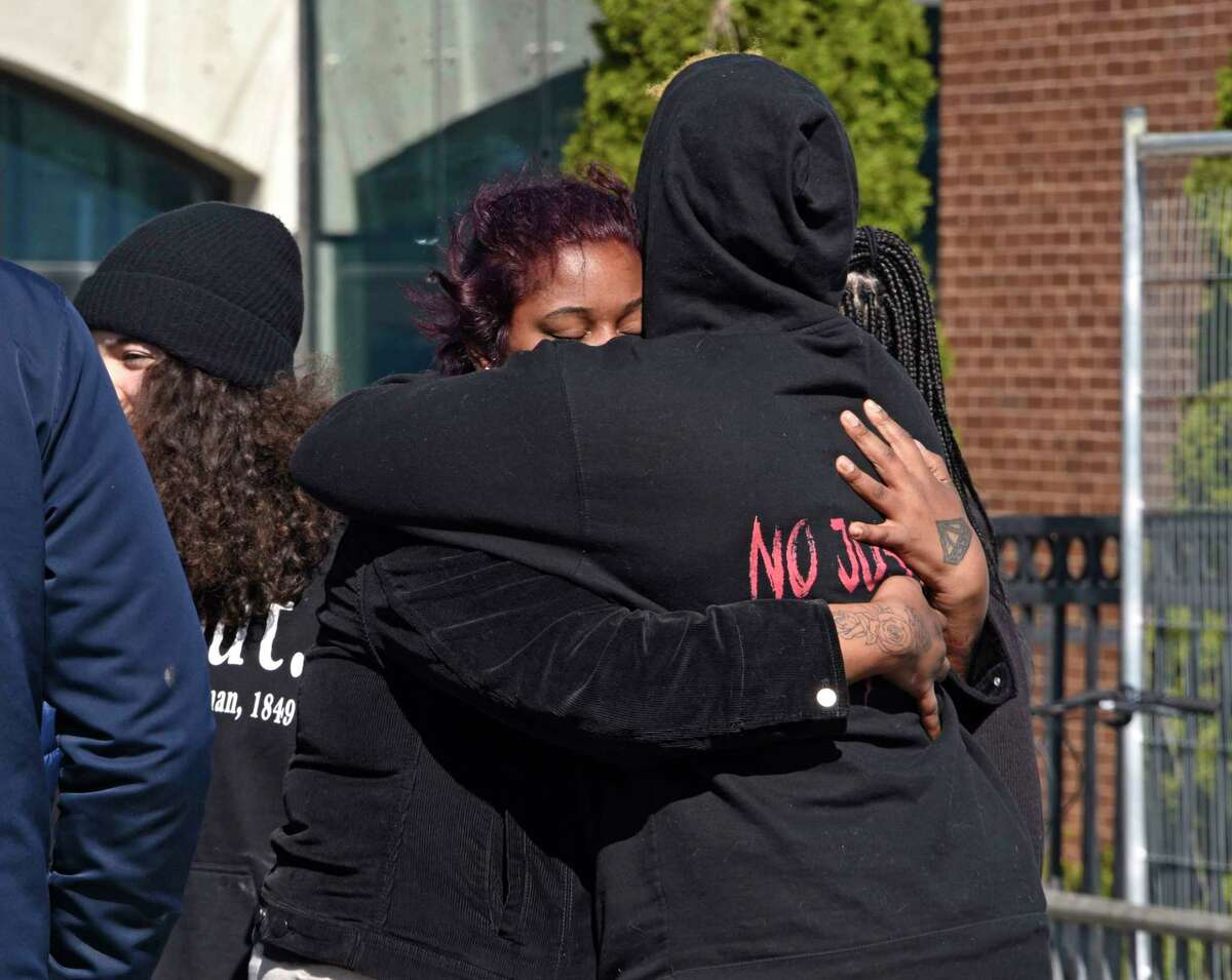 Activist are seen hugging during a protest in front of the Schenectady police headquarters on Friday, April 23, 2021 in Schenectady, N.Y. (Lori Van Buren/Times Union)