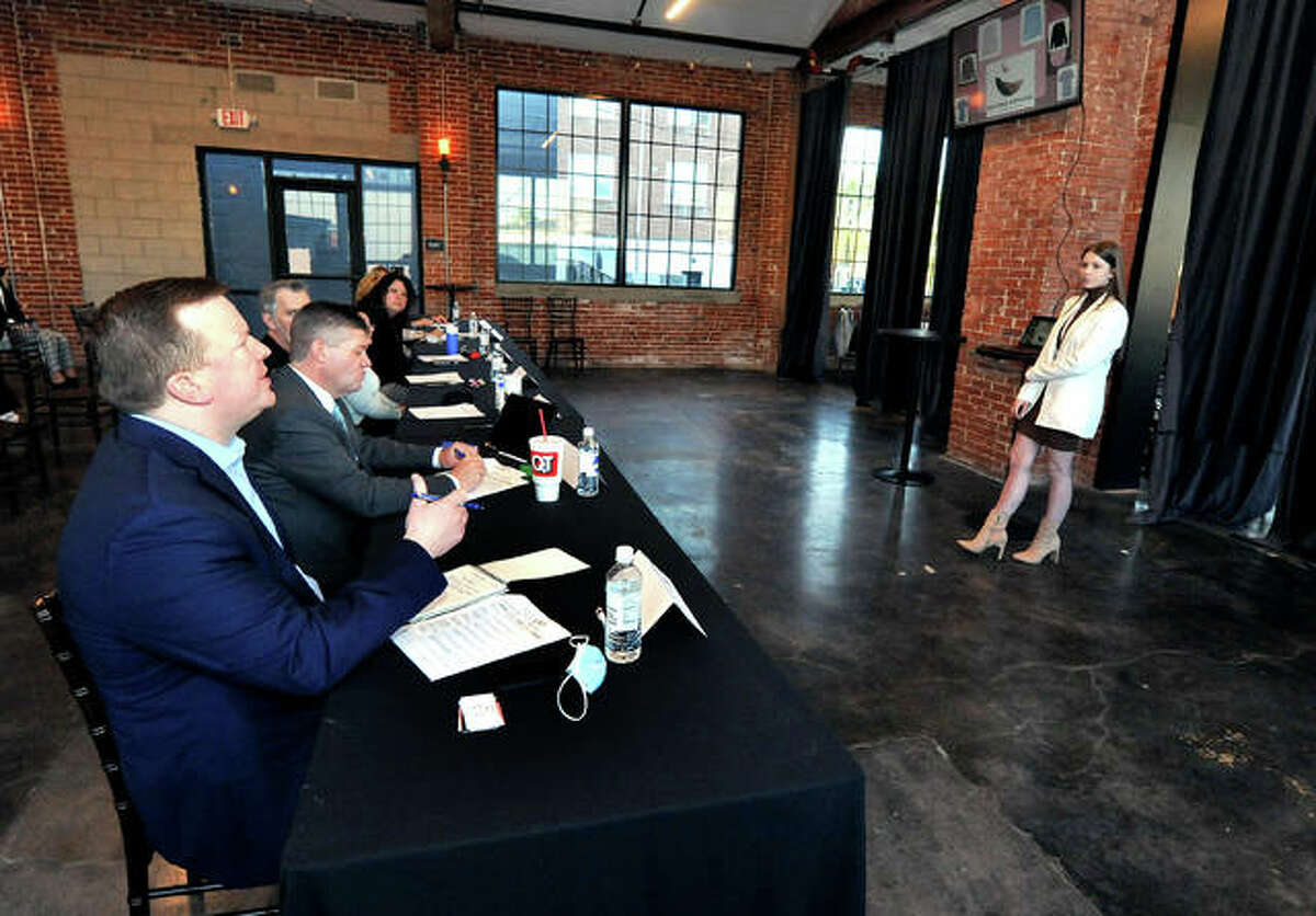 One of the Fish Tank judges State Sen. Jason Plummer, left, asks contestant Allison Biver, 17, of Metro-East Lutheran High School, right, a question about her presentation during the Edwardsville CEO Fish Tank Thursday at The Ink House.