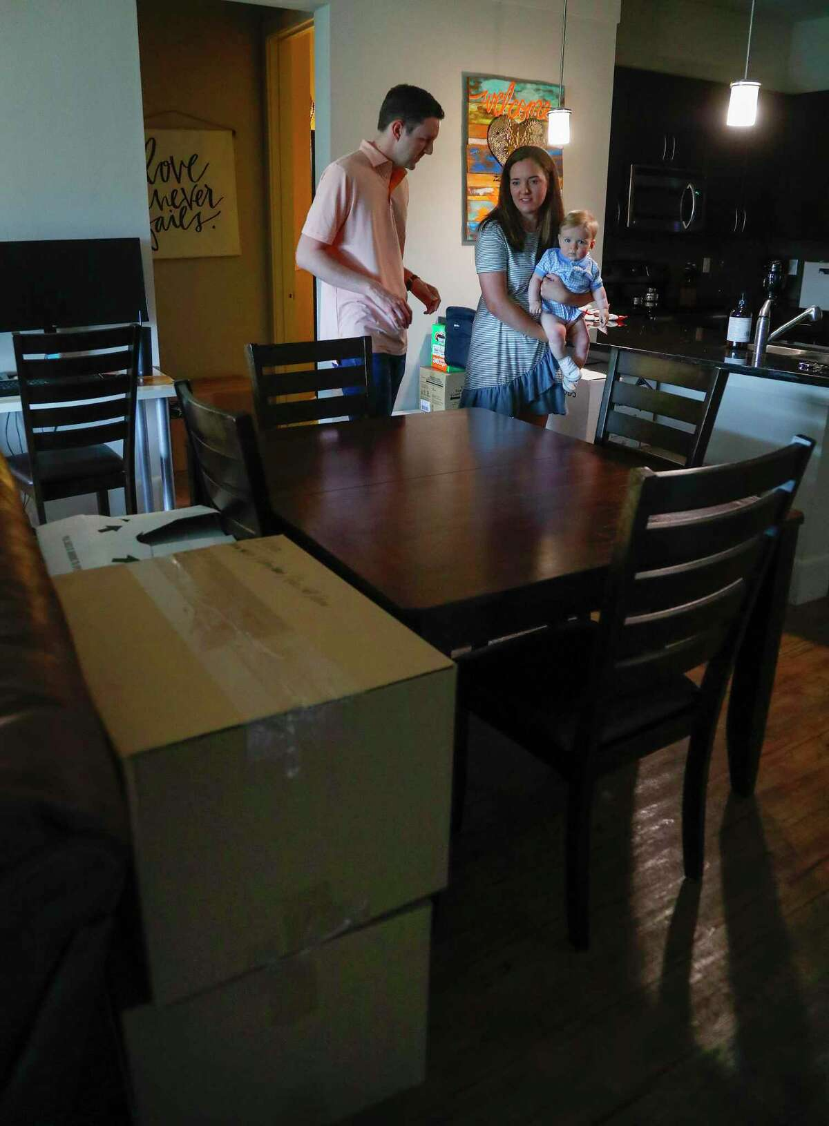Nick and Aly O'Neal, with their 8-month-old son, Shepherd, work around moving boxes as they are preparing to close on a house in Sugar Land and will be moving out of their apartment, in Houston, Monday, April 19, 2021. he first time home buyers are paying well over the asking price for the house, which was listed for $255,000 and drew 22 offers shortly after hitting the market.