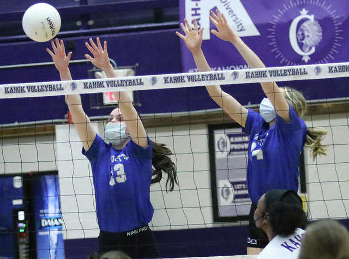 Marquette Catholic's Abby Williams (left) and Kylie Murray put up a block in a match against Collinsville in the season opener March 17 at Collinsville. The Explorers closed their season Thursday like they began it, with a victory that put their record at 12-7.