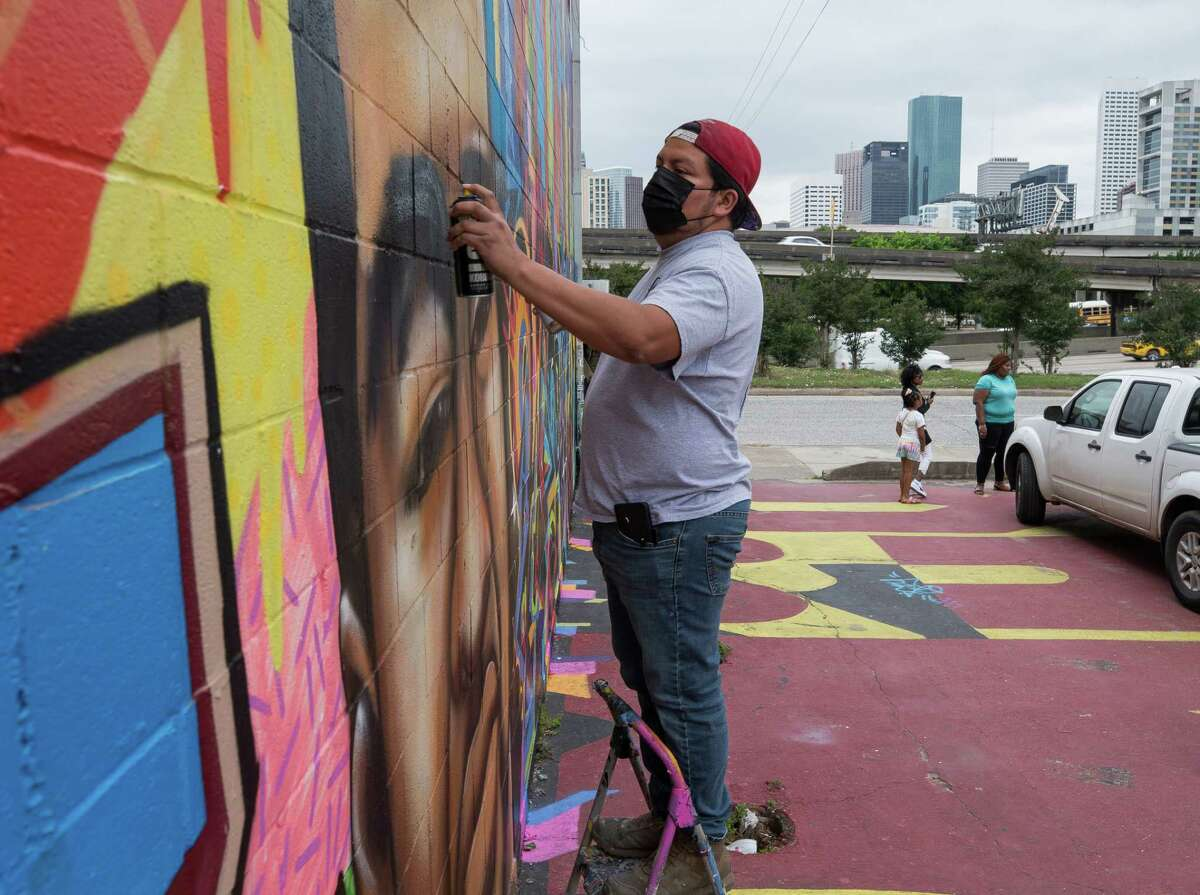Artist Carlos Alcaraz works to restore a George Floyd mural which was vandalized on Thursday, April 22, 2021,in the East Downtown neighborhood in Houston.