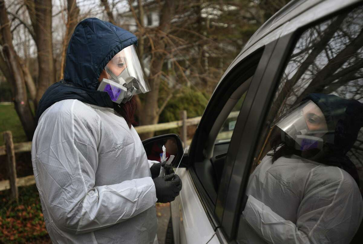 Megan Adams, of Branford, administers Covid-19 swab tests during the opening day of Griffin Hospital's drive through testing site at Unity Park in Trumbull, Conn.