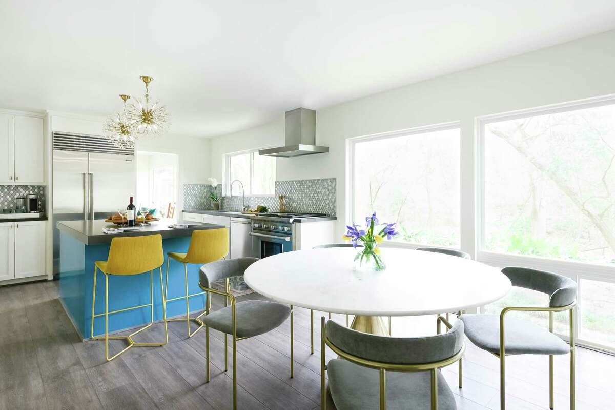 A peacock blue island and chartreuse barstools provide big pops of color in the kitchen and breakfast area.