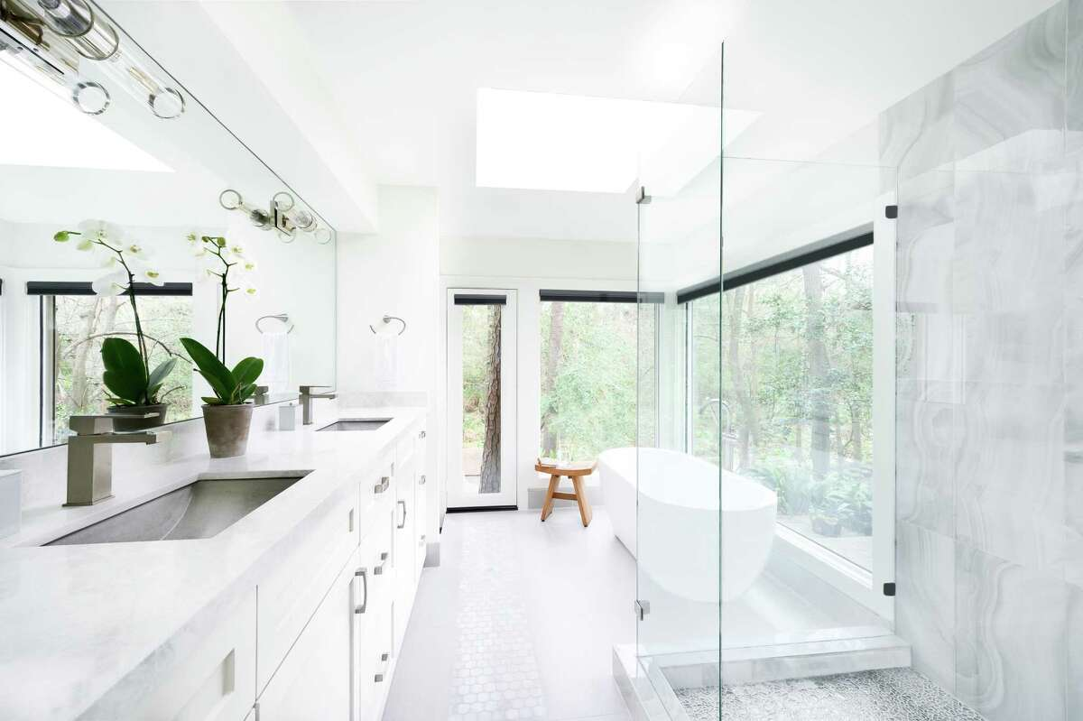 The primary bathroom originally was dark and felt closed in. Big windows bring in natural light and glass shower walls and gray-white tile are on-trend finishes.