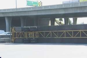 An overturned semi-truck shut down Highway 101 in San Jose on Friday morning.