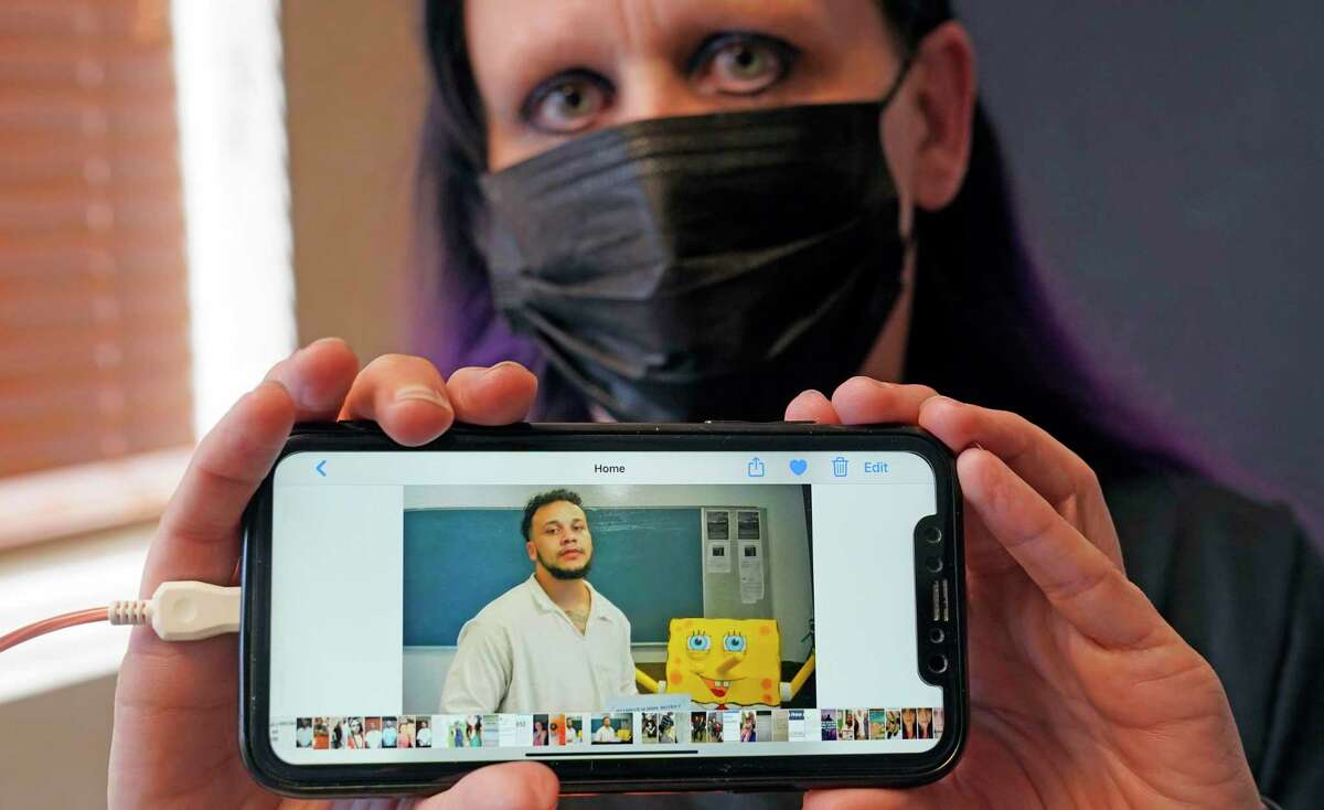Carrie Shipp shows a photo of her incarcerated 21-year-old son Matthew Shipp that she keep on her cell phone Friday, April 2, 2021, in Irving, Texas. Fewer than 20 percent of state and federal prisoners have received a COVID-19 vaccine, according to data collected by The Marshall Project and The Associated Press. Carrie Shipp said her son decided not to get vaccinated out of fear and distrust of prison medical staff. (AP Photo/LM Otero)
