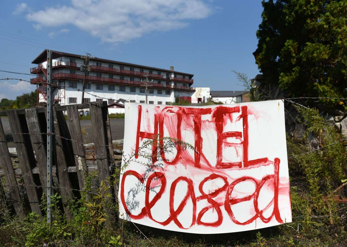 """A closed sign outside the old Friar Tuck resort in 2020. The Friar Tuck Inn, a storied Catskills resort whose new owners say they want to develop into a """"mindfulness"""" resort, was the scene of """"paramilitary maneuvers"""" last month with people toting replica AK-47s and using realistic explosive discharges, according to a lawsuit by the town."""