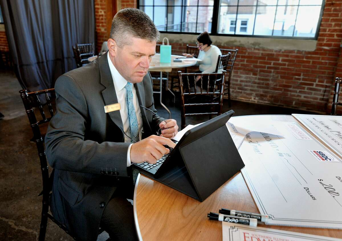 One of the CEO Judges, Stephen Cooper of First Mid Bank and Trust, tallies of scores during the judging at the Edwardsville CEO Fish Tank Thursday at the Ink House.
